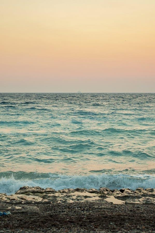 Orange sunset or sunrise to the the roaring Aegean sea in Rhodes, Greece stock image