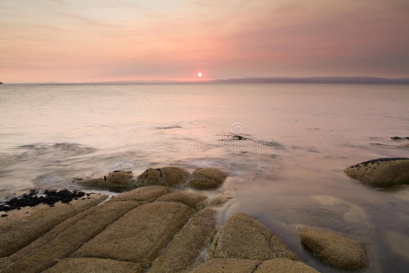 Orange Sunset Water. Pink sunset light on a coastal scene with blurred water stock photos