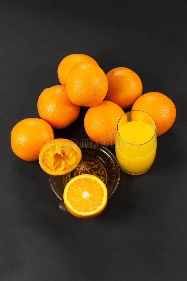 Orange sur l'obscurité avec le presse-fruits manuel photographie stock libre de droits