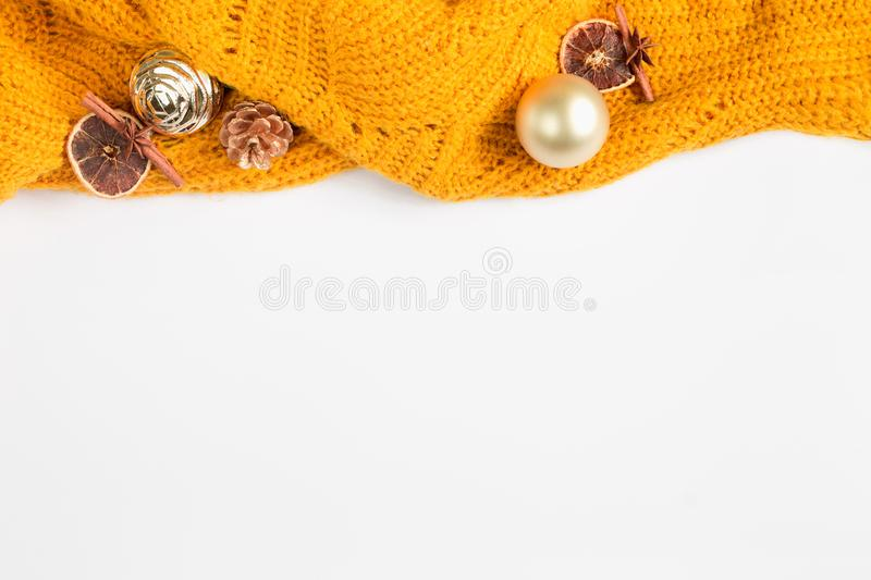 Orange sweater with Christmas toys on a white background, winter flat lay, top view, copy space. Christmas toys, yellow sweater, stock photography