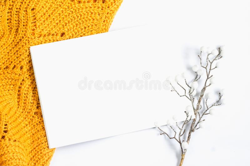 Orange sweater, a sheet of white paper and a decorative twig on a white background, greeting card, place for text. Winter flat lay royalty free stock photography