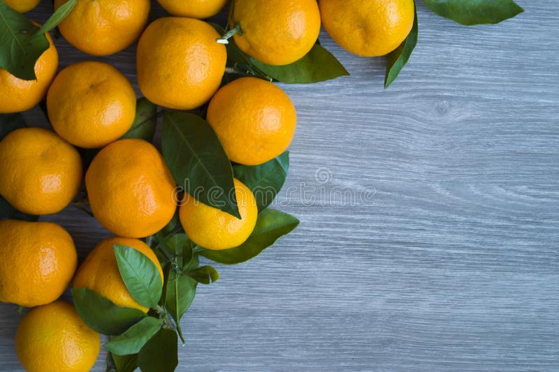 Orange sweet tangerines with green leaves on wooden background royalty free stock photos
