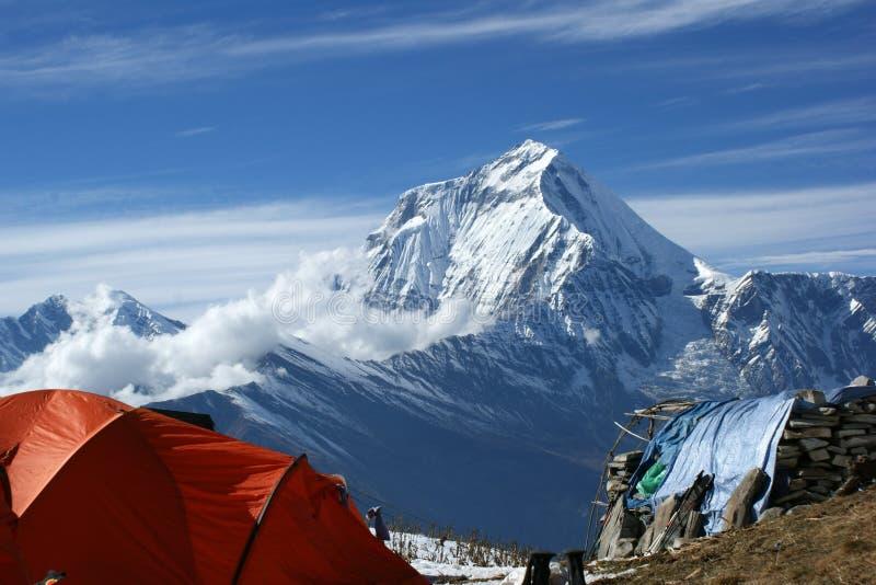 Orange tält i bakgrunden av bergen av Nepal fotografering för bildbyråer