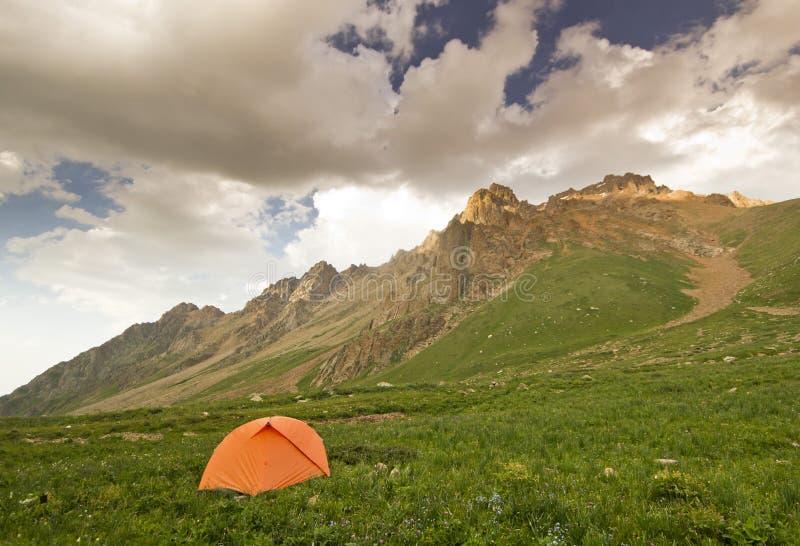 Orange tält på gröna kullar i höga berg på solnedgången royaltyfri foto