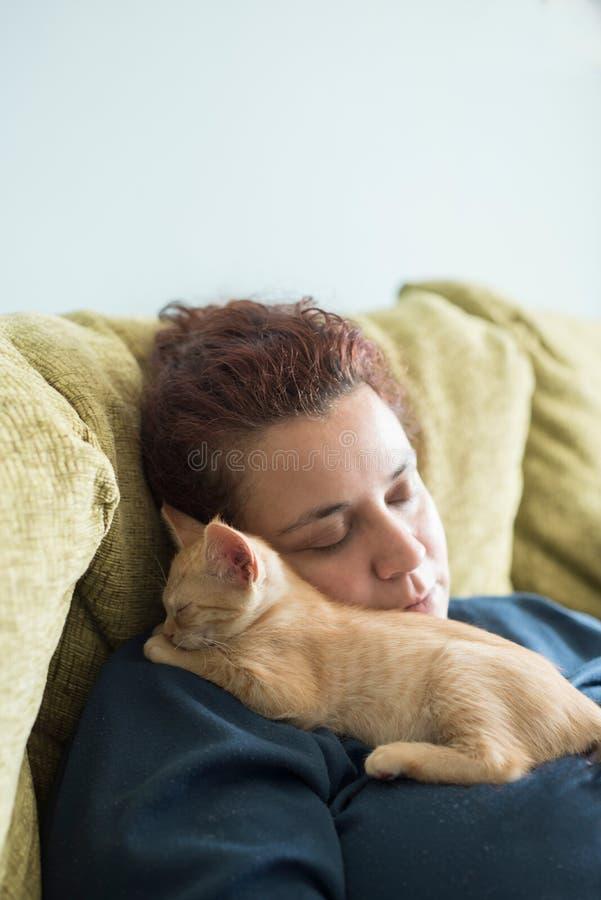 Orange tabby kitten sleeping in the lap of a woman royalty free stock photo