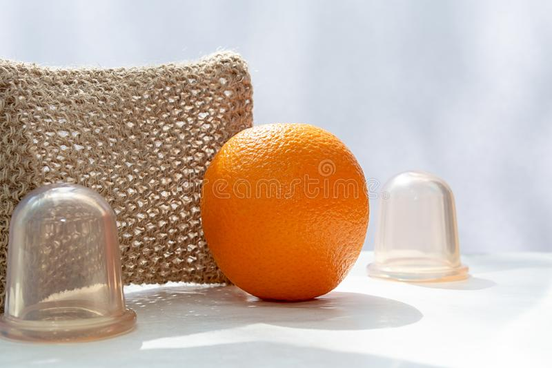 An orange is on the table and next to it are vacuum cans and a mesh washcloth made from natural fibers. stock photography