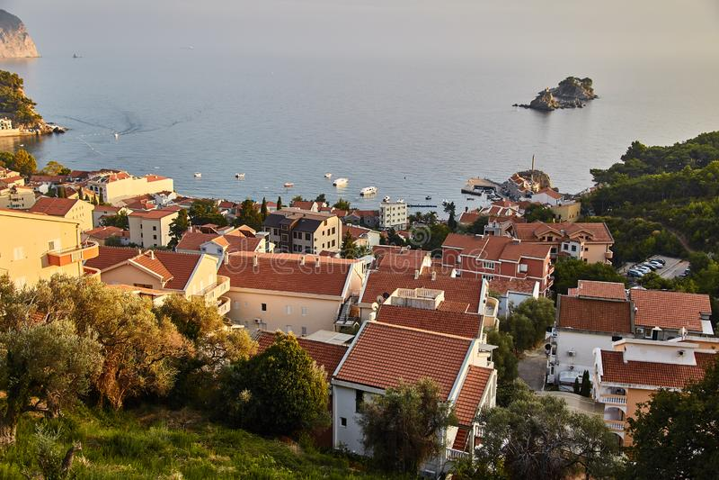 Orange tak av hus i Montenegro Staden av Petrovac Solnedgång arkivbild