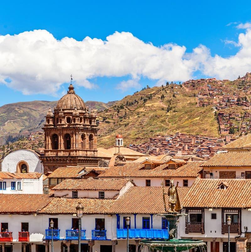 Orange tak av peruanska hus med springbrunnen av den Incan kejsaren Pachacuti och Basilika De La Merced på Plaza De Armas, Cuzco, royaltyfri foto