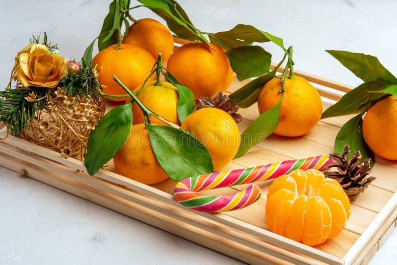 Orange tangerin med sidor på en vit bakgrund i en korg, nytt år royaltyfria bilder
