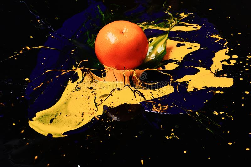 Orange or tangerine covered with paints. Nutrition and food art. Concept. Drops of blue and yellow oil or acrylic paint poured on fruit on black background royalty free stock photography