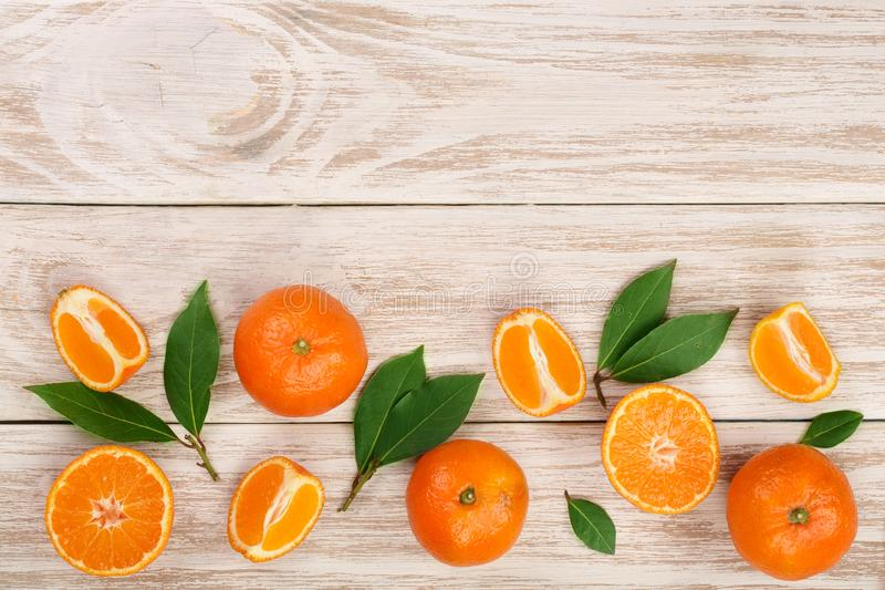 Orange or tangerine with leaves on white wooden background. Flat lay, top view. Fruit composition.  royalty free stock images