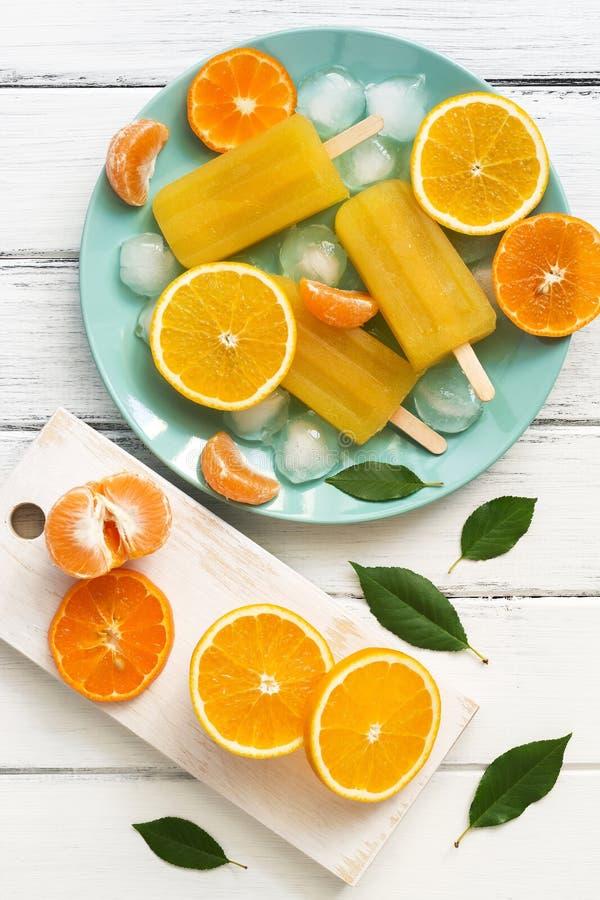 Orange - Tangerineeis am stiel in der blauen Platte mit Eiswürfeln und Scheiben der Frucht, weiße hölzerne rustikale Tabelle Drau stockbilder