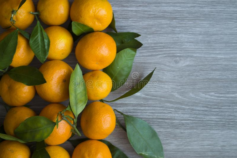 Orange tangerines with green leaves on wooden background royalty free stock photography