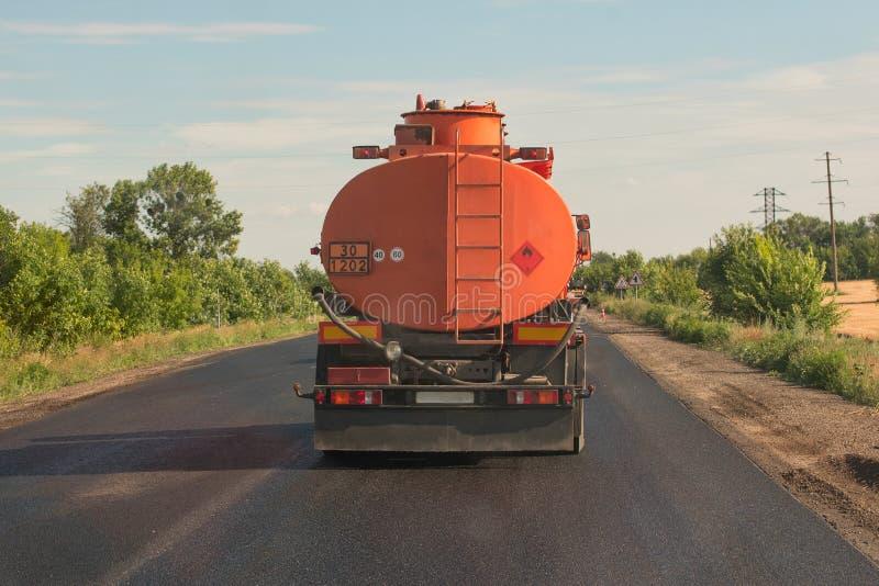 Orange Tankwagenfahrten auf eine Landstraße gegen einen blauen Himmel Rückseitige Ansicht stockfotografie