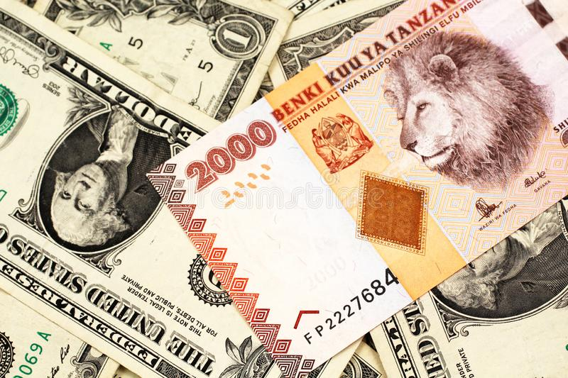 An orange Tanzanian shilling note with American one dollar bills. A close up image of a two thousand Tanzanian shilling bank note on a background of American one royalty free stock photography