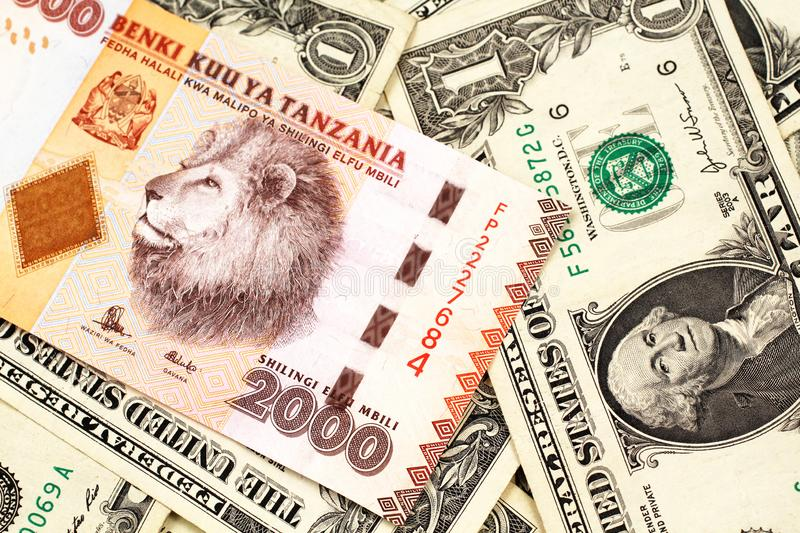 An orange Tanzanian shilling note with American one dollar bills. A close up image of a two thousand Tanzanian shilling bank note on a background of American one royalty free stock images