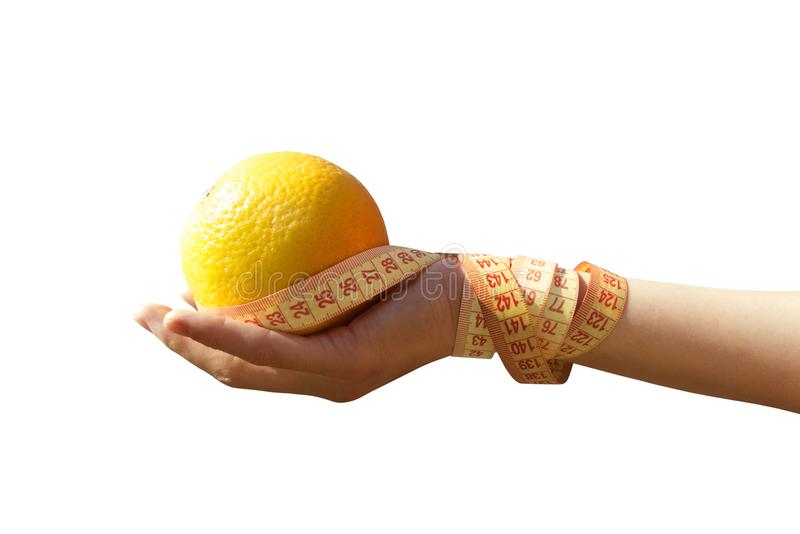 Orange and tape measure in hand on a white background royalty free stock photos