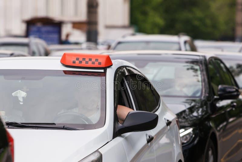 Orange taxisymbol i biltrafikstockningen på det vita taket arkivbild
