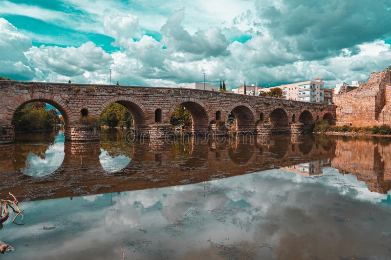 Orange and teal view of the Roman bridge of Merida with its reflection on the Guadiana river. royalty free stock images