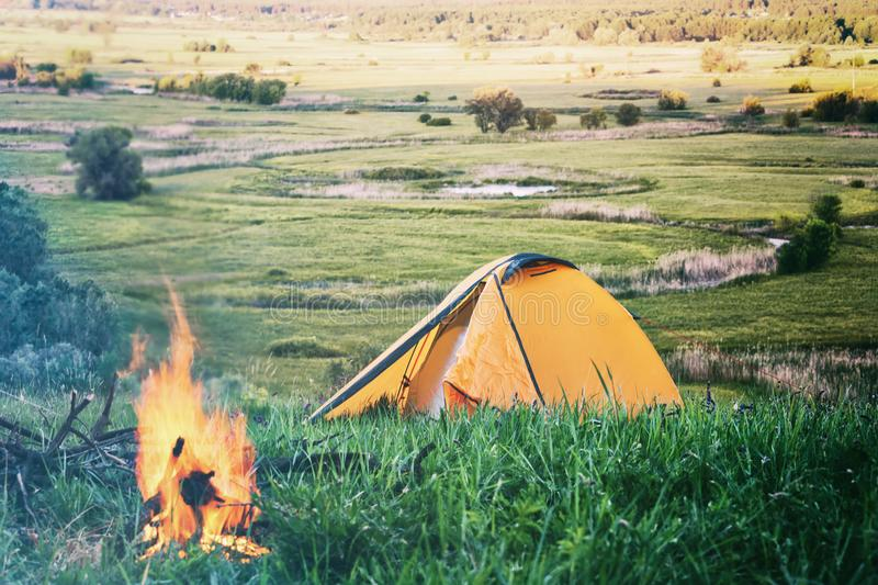 Orange tent with fire in field with green grass stock photo
