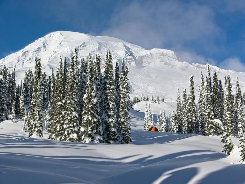 Orange Tent on a Snowy Field with Mt. Rainier in the Background royalty free stock photo