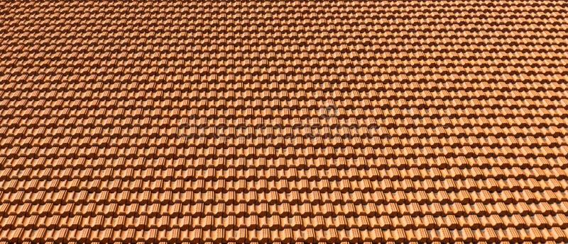 Orange textur eller bakgrund för tegelplattatak på den soliga dagen arkivbilder