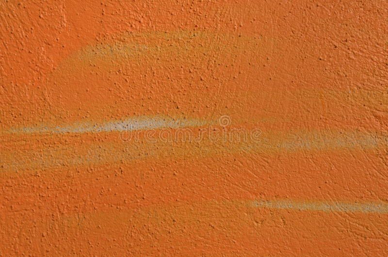 Orange textured wall. Textured wall airbrushed by orange graffiti paint royalty free stock photos