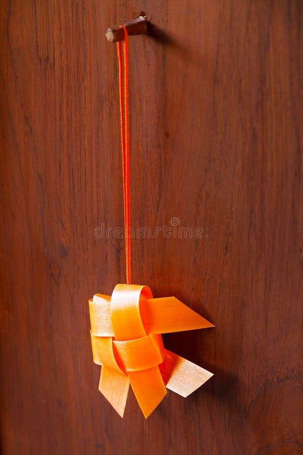 Orange thailändische traditionelle gesponnene bewegliche Fische des Bandes Gold, diean der Holztür hängen lizenzfreies stockbild
