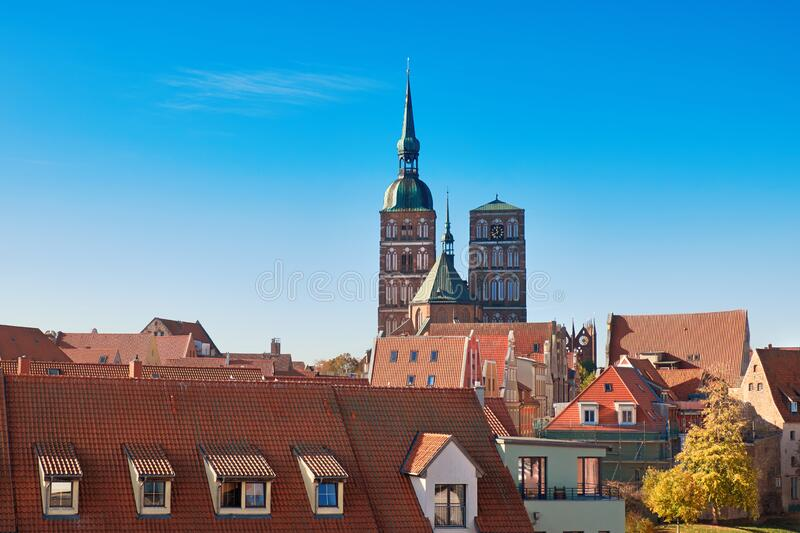 Orange tiled roofs of Stralsund with towers of medieval parish Church of St. Nicholas stock images