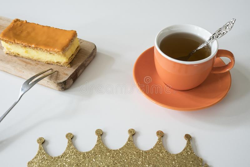 Orange tompouce, traditional Dutch treat with pudding and frosting on national holiday Kings Day April 27th, in The Netherlands. Dutch breakfast setting for stock photos
