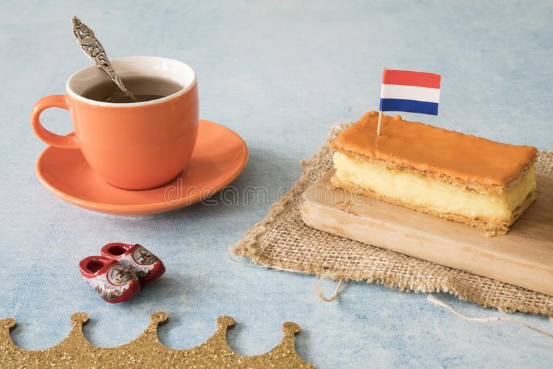 Orange tompouce, traditional Dutch treat with pudding and frosting on national holiday Kings Day April 27th, in The Netherlands. Dutch breakfast setting for royalty free stock photo