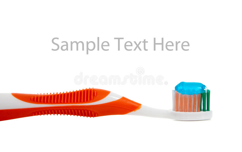 Orange toothbrush and toothpaste on white. A orange toothbrush and blue gel toothpaste on a white background stock images
