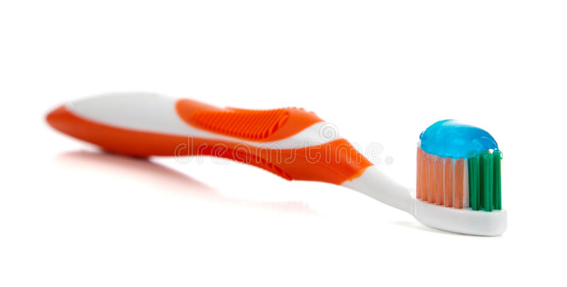 Orange toothbrush and toothpaste on white. A orange toothbrush and blue gel toothpaste on a white background stock photo