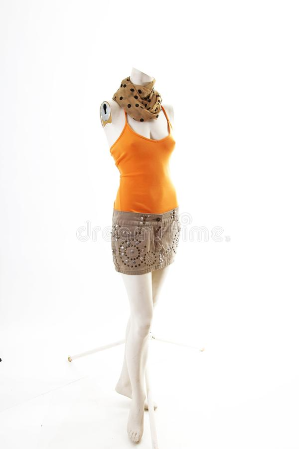 Orange top and beige mini skirt on mannequin full body shop display. Woman fashion styles, clothes on white studio background.  royalty free stock image