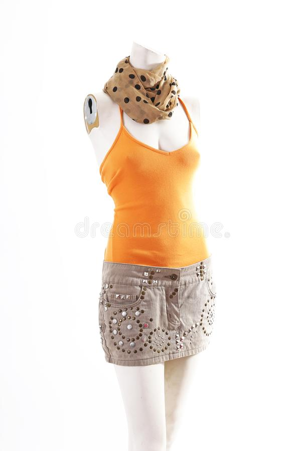 Orange top and beige mini skirt on mannequin full body shop display. Woman fashion styles, clothes on white studio background.  stock photography
