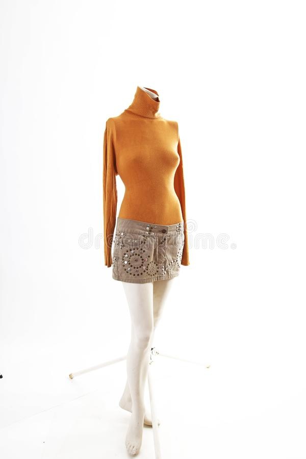 Orange top and beige mini skirt on mannequin full body shop display. Woman fashion styles, clothes on white studio background.  stock photo
