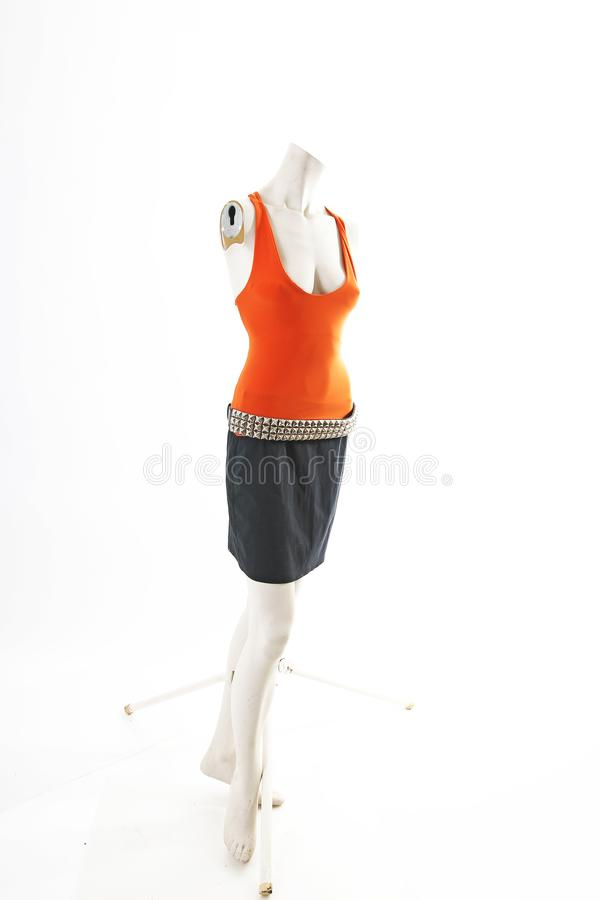 Orange top and black skirt on mannequin full body shop display. Woman fashion styles, clothes on white studio background. Cute stock image