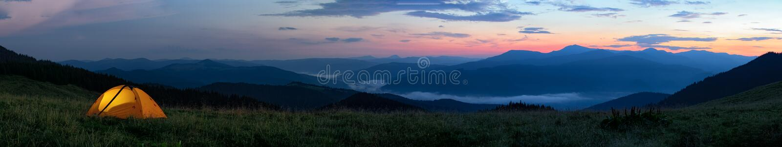 Orange tourist tent illuminated from inside stands in mountains above clouds royalty free stock photo