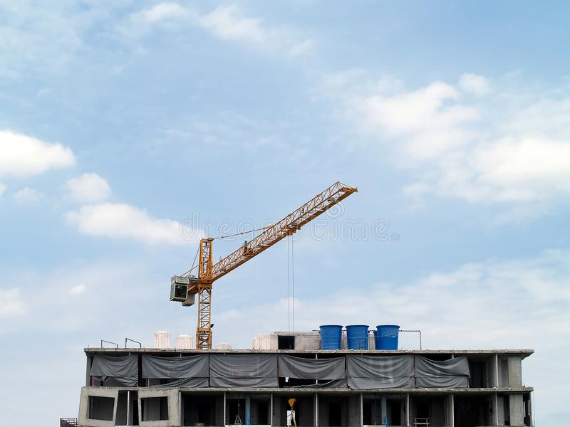 Orange tower crane at top of building is under construction with blue sky and cloud, construction high-rise building in the city. Construction high-rise building royalty free stock photo