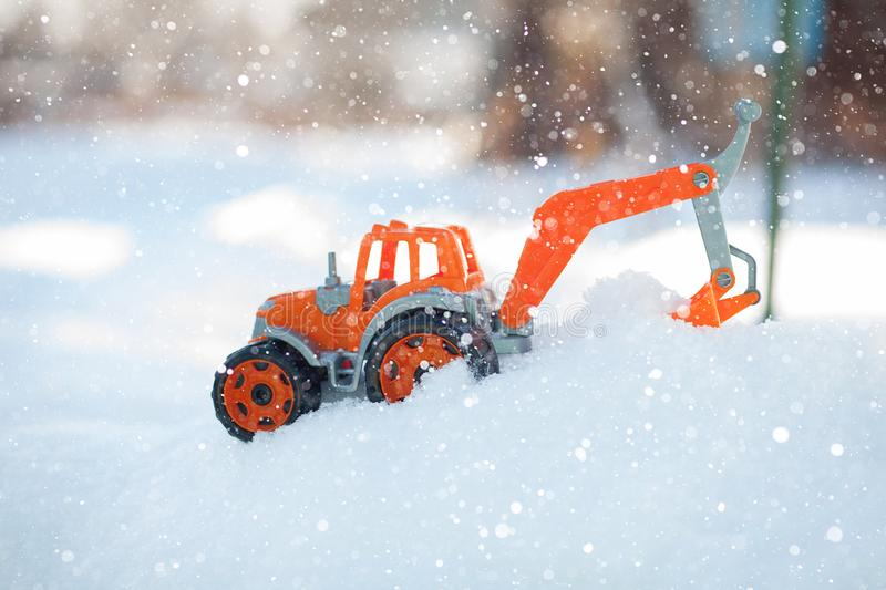 Orange toy tractor with large black wheels close-up, standing in the snow.  royalty free stock photos