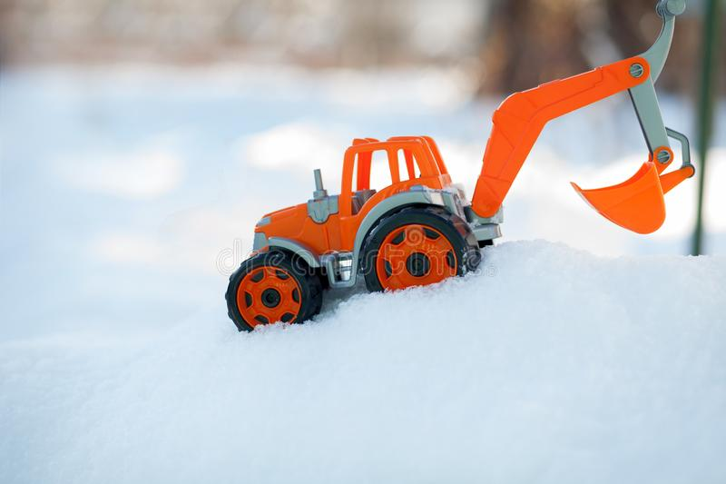 Orange toy tractor with large black wheels close-up, standing in the snow.  stock images