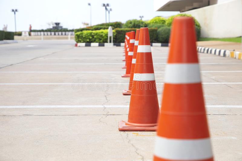 Orange traffic cones stand in a row on the parking. stock photos