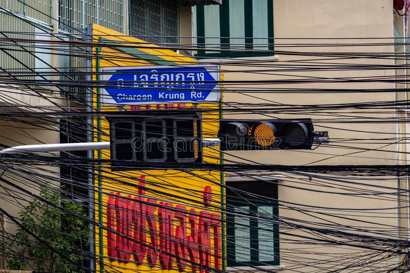Orange traffic light Bangkok old town. Bangkok, Thailand - May 1, 2018: Orange light switched on a traffic light surrounded by road signs and electricity cables stock photography