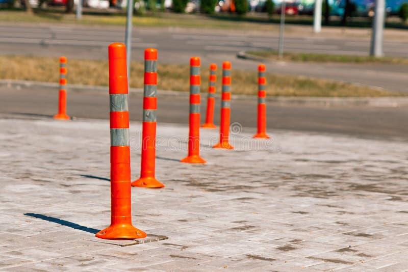 Orange traffic pillar on the road and on parking lane.  stock photo