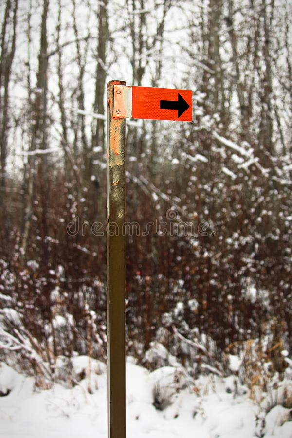 An orange trail marker sign along a hiking path stock images