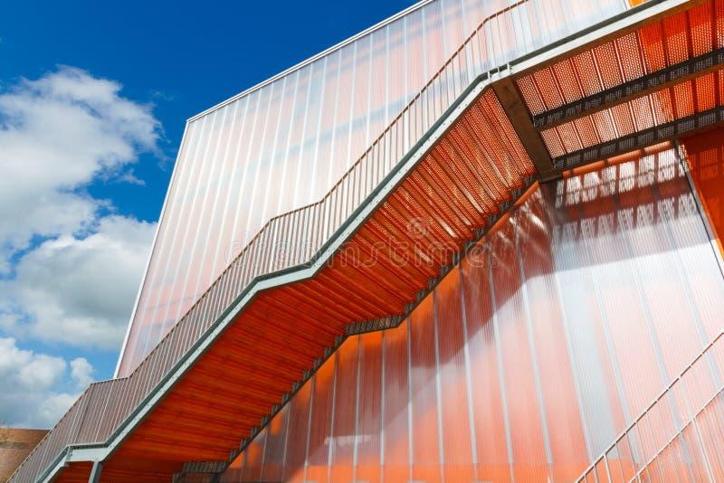 Orange Treppe auf der Außenseite des modernen Gebäudes stockbilder
