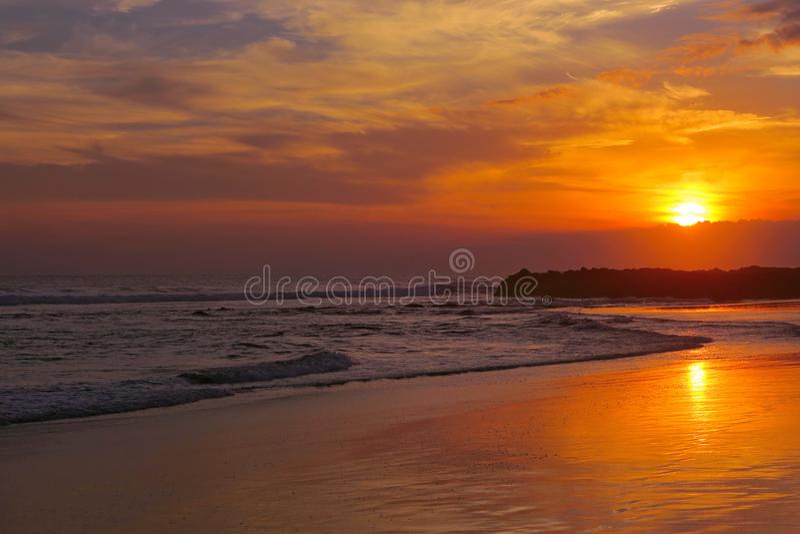 Orange tropical sunset with reflection at Canggu beach, Bali, Indonesia royalty free stock photo