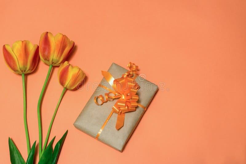 Orange tulpan och gåvaask som slås in i kraft papper med den orange pilbågen på ljus peachy bakgrund Härlig vårorientering hälsni arkivfoto
