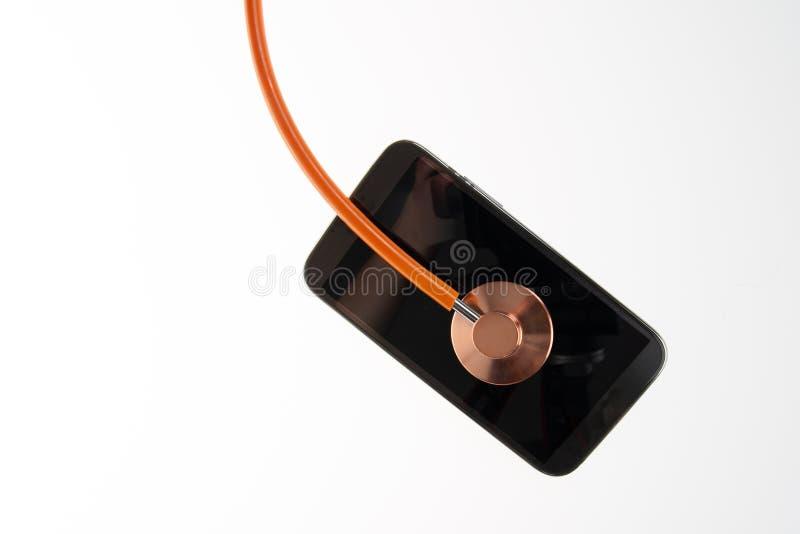 Orange tunn linje stetoskop med mobiltelefonen som isoleras på det vita bakgrundsbegreppet av rådgivning, refit, kontroll, första royaltyfri fotografi