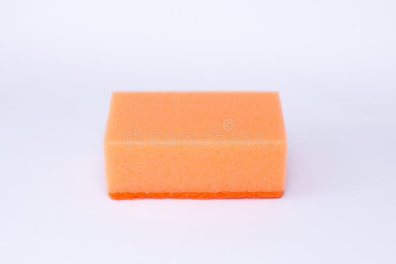 Orange tvättlapp för tvättande disk på en vit bakgrund arkivbild